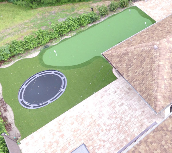 In ground trampoline and artificial turf yard