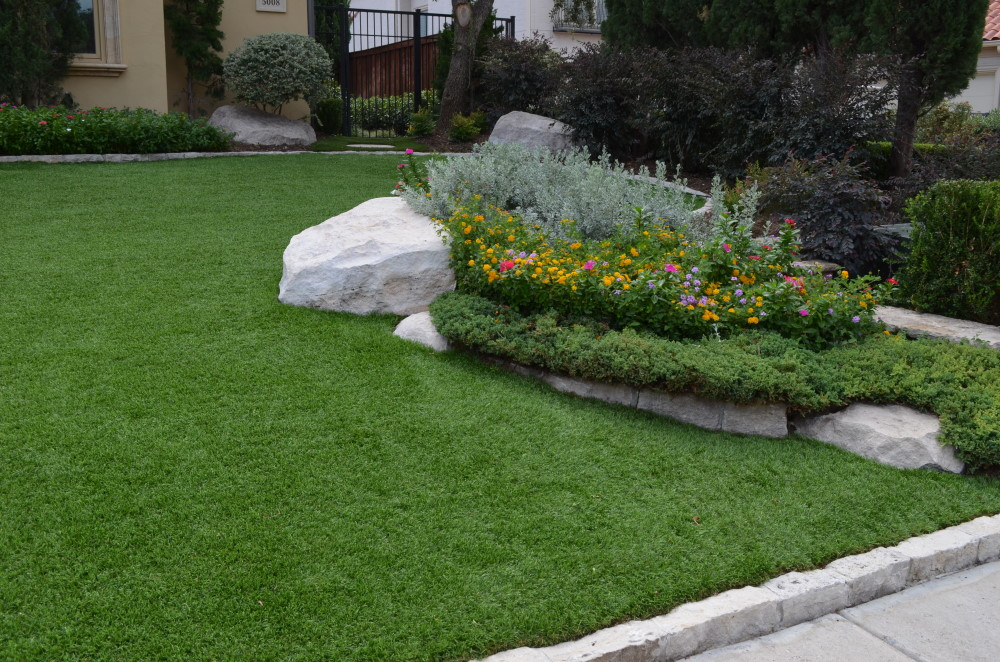 Garden and rocks surrounded by artificial grass