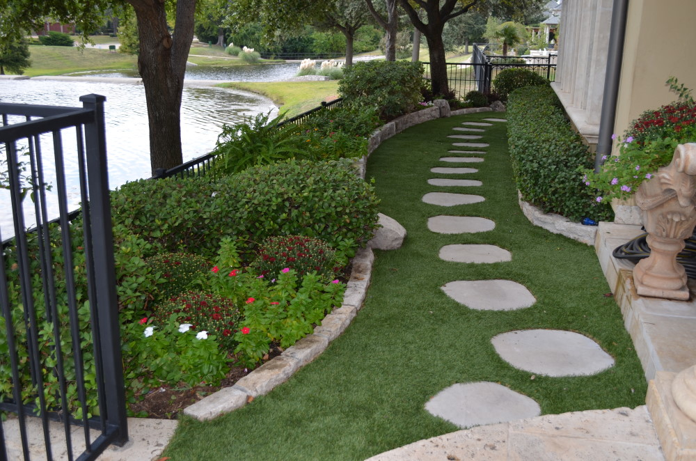 Stepping stones next to landscaped garden with artificial grass