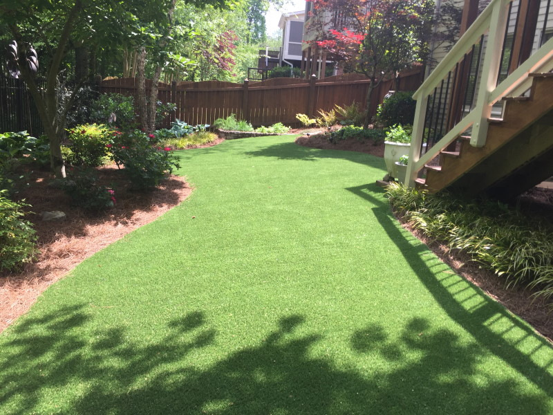 Stairs leading down to yard using artificial grass