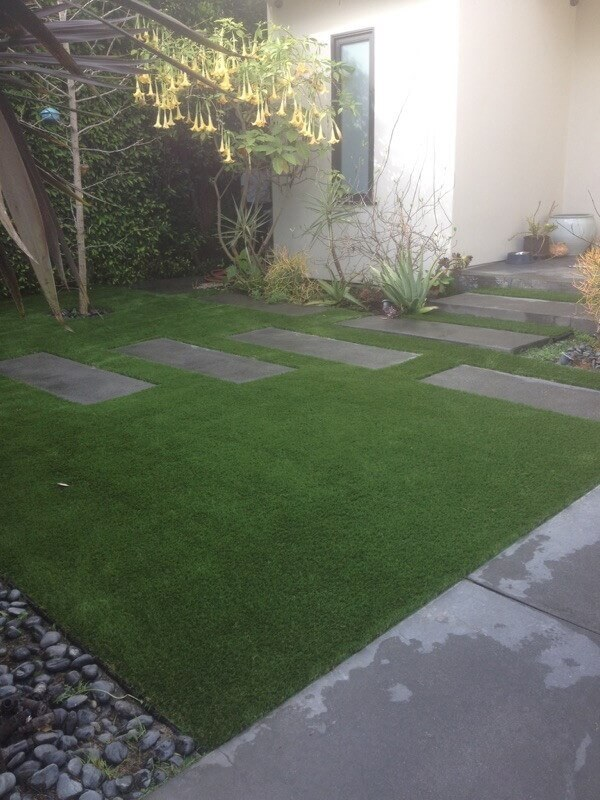 backyard with stepping stones on artificial grass
