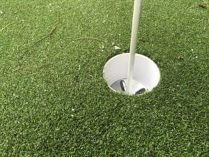 close up of putting green hole surrounded by artificial grass