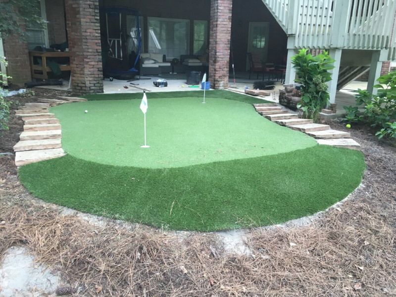 backyard patio connected to small putting green using artificial grass