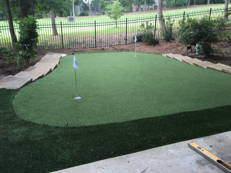 backyard patio looking at newly installed putting green