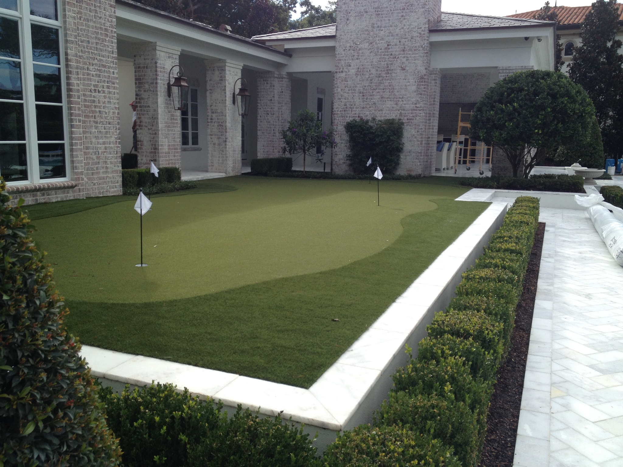 medium size golf green and fringe by stone house