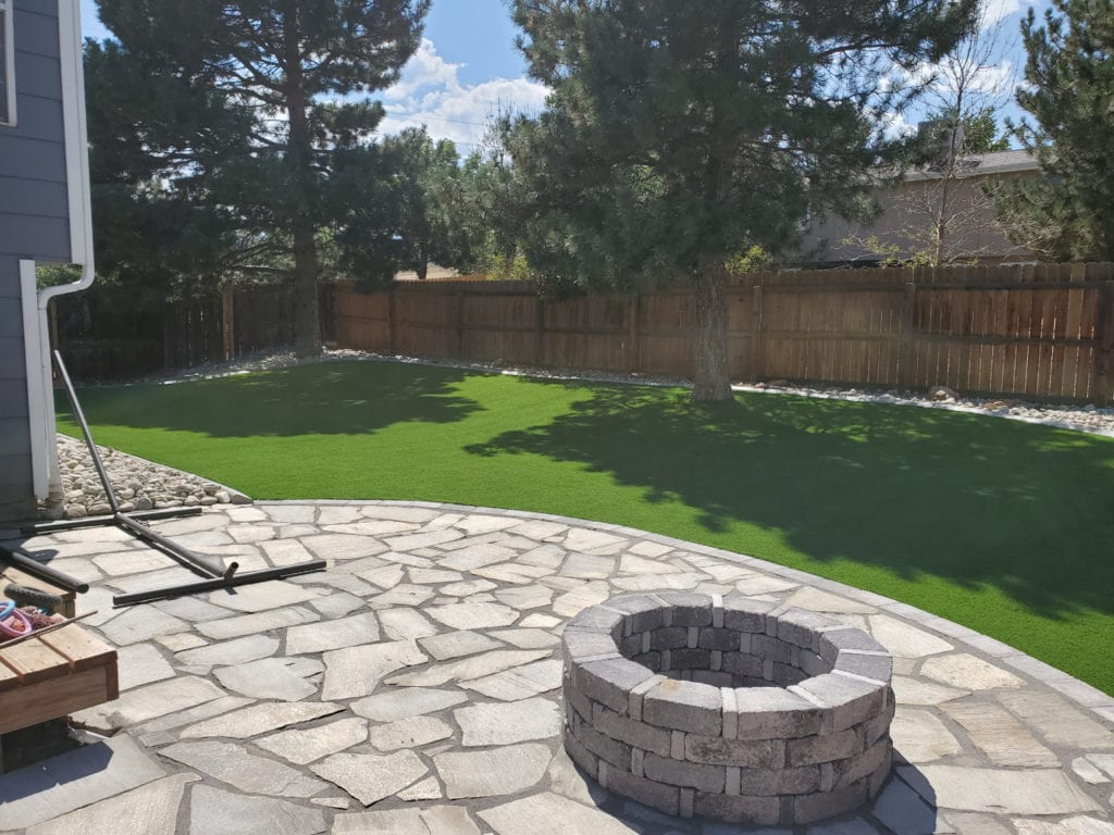Nice backyard with stone patio and firepit with artificial grass surround