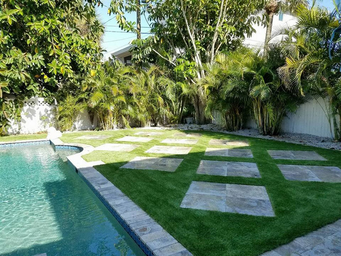 artificial grass around pool with pavers