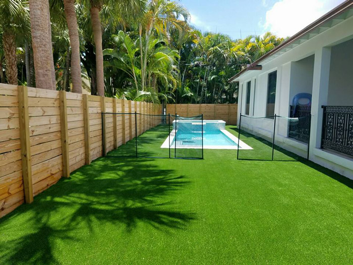 large backyard with artificial grass around pool
